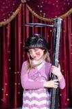 Arma vestindo de Make Up Holding do palhaço da menina grande Fotografia de Stock