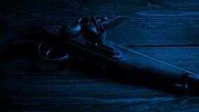 Arma viejo de la pistola en la tabla en la oscuridad almacen de video