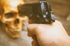 Arma y cráneo, aún vida Imagen de archivo libre de regalías