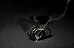 Arma y humo Imagen de archivo
