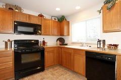 Armadi da cucina di Brown con gli apparecchi neri Fotografia Stock