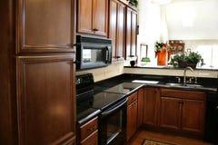 Armadietti di legno della cucina neri e stufa inossidabile immagini stock libere da diritti