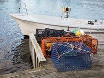 Armadilhas da lagosta e do caranguejo que estão em um cais ao lado de um bote foto de stock