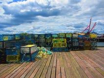 Armadilhas da lagosta empilhadas em um cais da pesca Fotografia de Stock Royalty Free