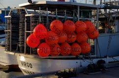 Armadilhas e flutuadores vermelhos brilhantes prontos para a ação em um barco comercial do caranguejo na noite fotografia de stock