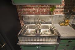 Armadio da cucina con il doppio lavandino d'acciaio nello stile inglese, tavola verde, cucina di lusso d'argento del rubinetto Immagini Stock Libere da Diritti