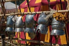 Armaduras metálicas penduradas na linha na frente da barraca vermelha e amarela Imagens de Stock Royalty Free