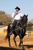 Armand il cowboy di canto sul suo stallone nero Fotografia Stock Libera da Diritti