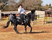 Armand il cowboy di canto sul suo stallone nero Immagini Stock