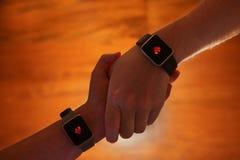 Armar ambraced visa hjärtasymboler på smarta klockor fotografering för bildbyråer