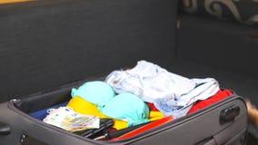 Armar av den unga kvinnan öppnar en resväska och packar upp personligt material Ankomst från semesterorten Kvinnliga händer lägge lager videofilmer