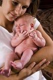 armar behandla som ett barn henne den nyfödda holdingmodern Arkivfoto