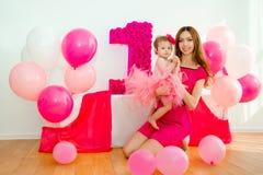 armar behandla som ett barn henne holdingmodern Liten flicka i en rosa kjol Royaltyfria Bilder