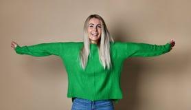 Armar för ung kvinna som är utsträckta av studioväggen som tycker om frihet och liv arkivfoto