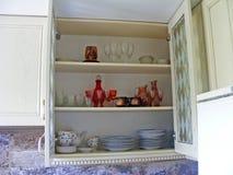Armario de cocina cercano para arriba con los estantes y los vidrios de cristal Imágenes de archivo libres de regalías