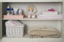 Armario del bebé con su materia colocada en estantes Imagen de archivo libre de regalías