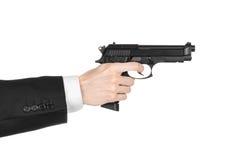 Armas de fogo e assunto da segurança: um homem em um terno preto que guarda uma arma em um fundo branco isolado no estúdio Foto de Stock Royalty Free