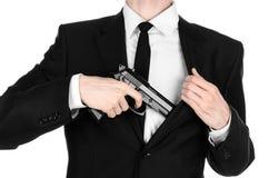 Armas de fogo e assunto da segurança: um homem em um terno preto que guarda uma arma em um fundo branco no estúdio Imagens de Stock