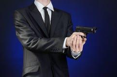 Armas de fogo e assunto da segurança: um homem em um terno preto que guarda uma arma em uma obscuridade - fundo azul no estúdio i Fotografia de Stock Royalty Free