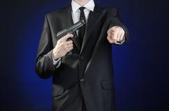 Armas de fogo e assunto da segurança: um homem em um terno preto que guarda uma arma em uma obscuridade - fundo azul no estúdio i Fotos de Stock Royalty Free