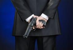Armas de fogo e assunto da segurança: um homem em um terno preto que guarda uma arma em uma obscuridade - fundo azul no estúdio Fotos de Stock Royalty Free