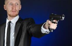 Armas de fogo e assunto da segurança: um homem em um terno preto que guarda uma arma em uma obscuridade - fundo azul no estúdio Fotografia de Stock