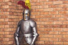 Armatura medievale del cavaliere contro lo sfondo di un muro di mattoni Fotografia Stock