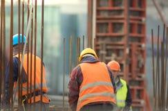 Armature και εργαζόμενοι στο πορτοκάλι στο εργοτάξιο οικοδομής Στοκ Φωτογραφία