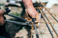 Armature bars in construction site, hands of builder man, construction worker on site Royalty Free Stock Images