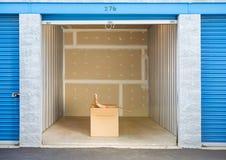 Armazenamento: Caixa de fechamento da mulher na unidade de armazenamento imagens de stock