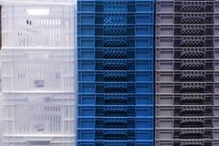 Armazenamento da pilha de caixas brancas, cinzentas e azuis coloridas novas do recipiente plástico imagem de stock royalty free