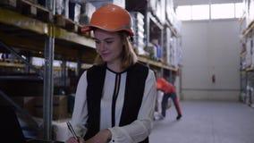 Armazene a mulher do trabalhador no portátil do uso do capacete de segurança e faça anotações no bloco de notas filme