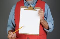 Armazene o trabalhador que aponta à placa de grampo Imagens de Stock Royalty Free