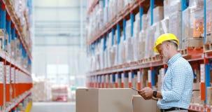 Armazene o trabalhador que usa a tabuleta digital ao verificar pacotes filme