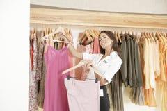 Armazene a roupa de trabalho e de suspensão do assistente na loja fotos de stock royalty free