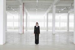 Armazém de Standing In Empty da mulher de negócios Fotografia de Stock Royalty Free