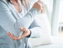 Armbåge för ` s för Closeup kvinnlig Armen smärtar och skadan Hälsovård och med royaltyfri foto