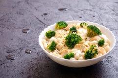 Armbågemakaroni med höna-, broccoli-, ost- och krämsås på mörk bakgrund arkivbild