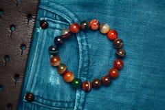 Armband auf dem Arm von Steinbällen gegen den Hintergrund von Jeans Stockbild