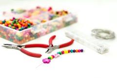 Armband van plastic parels voor meisjes onvolledig in proces wordt gemaakt dat Stock Fotografie
