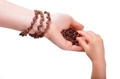 Armbandet från kaffebönor på ett kvinnligt räcker Arkivfoto