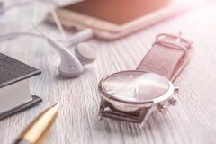 Armbandsur, mobiltelefon med hörlurar och en anteckningsbok med en penna på ett gammalt vitt kontorsskrivbord och kafé arkivfoto