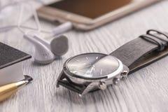 Armbandsur, mobiltelefon med hörlurar och en anteckningsbok med en penna på ett gammalt vitt kontorsskrivbord och kafé royaltyfri bild