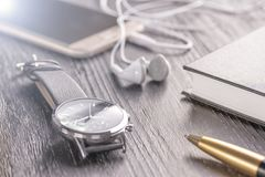 Armbandsur, mobiltelefon med hörlurar och en notepad med en penna på ett gammalt mörkt kontorsskrivbord royaltyfri fotografi