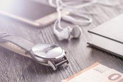 Armbandsur, mobiltelefon med hörlurar och notepad på det gamla mörka kontorsskrivbordet Närliggande är euroanmärkningen arkivbild