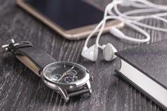Armbandsur, mobiltelefon med hörlurar och notepad på ett gammalt mörkt kontorsskrivbord royaltyfri foto