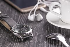 Armbandsur och mobiltelefon med hörlurar och en kopp kaffe på en mörk trätabell arkivfoton