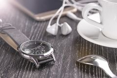 Armbandsur och mobiltelefon med hörlurar och en kopp kaffe på en mörk trätabell royaltyfri foto