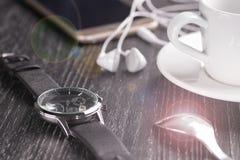 Armbandsur och mobiltelefon med hörlurar och en kopp kaffe på en mörk trätabell royaltyfri fotografi