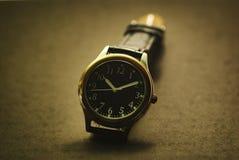 Armbanduhr auf einem dunklen Hintergrund stockfotos